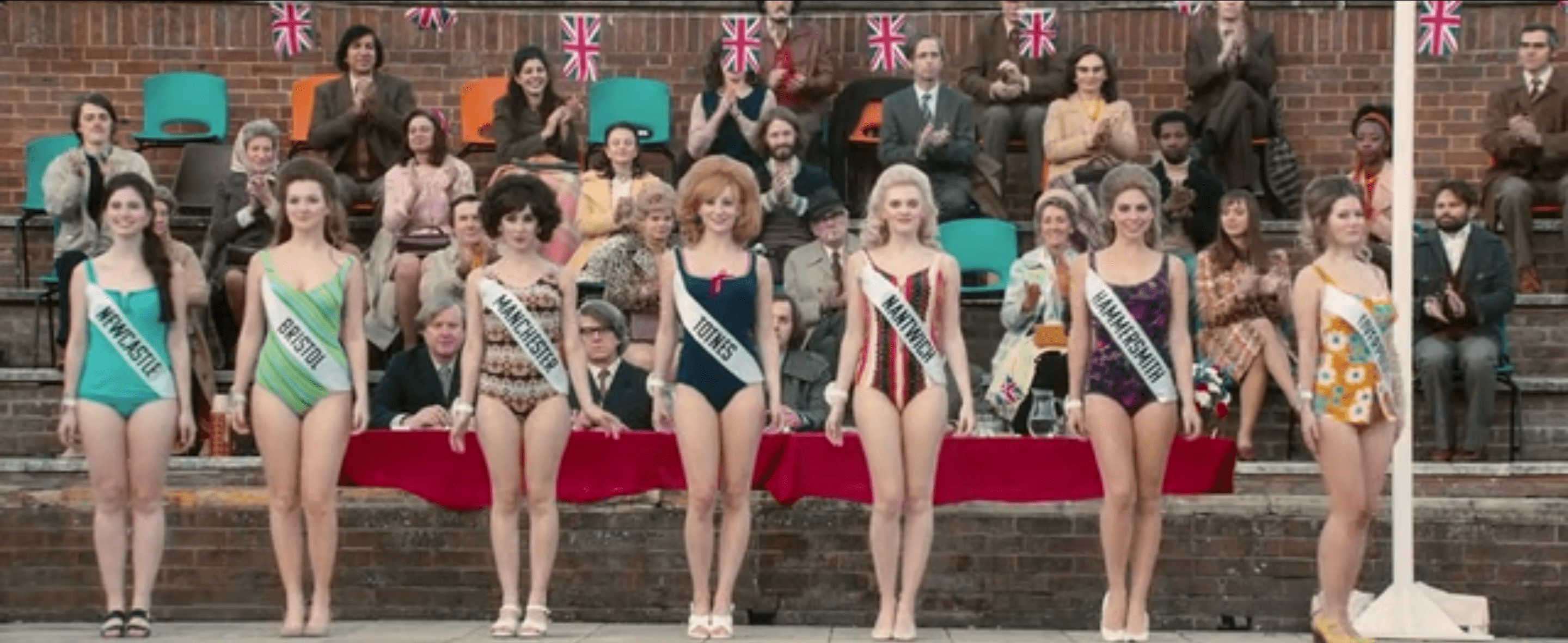 Pageant contestants wearing bathing suits lined up to be judged in front of a panel of men. Based on the way everyone else is dressed, it appears to be chilly outside.