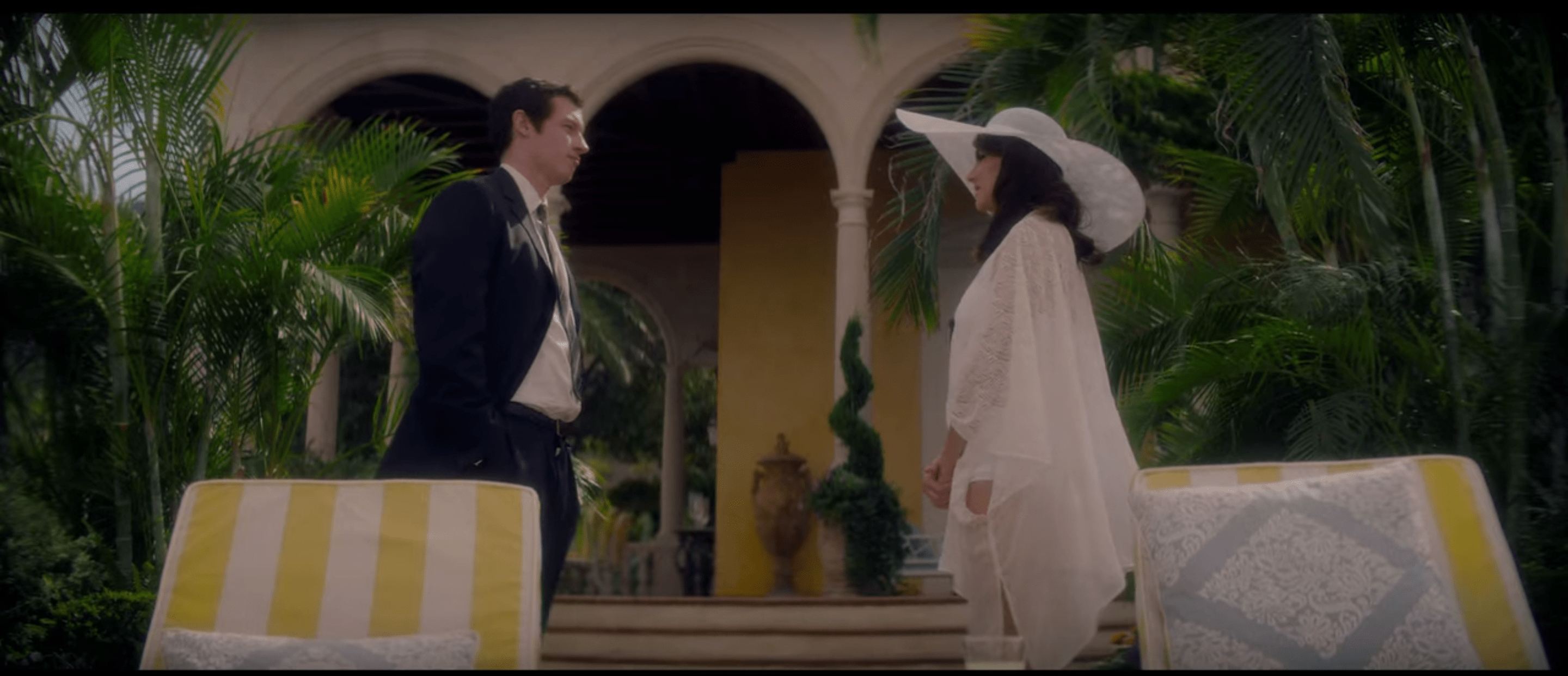 Anthony and Jennifer meeting for the first time. She is wearing a white floaty bathing suit cover up and huge white sun hat. He is dressed in a suit and tie. There are yellow and white striped lounge chairs in front of them and large fronded plants behind them.