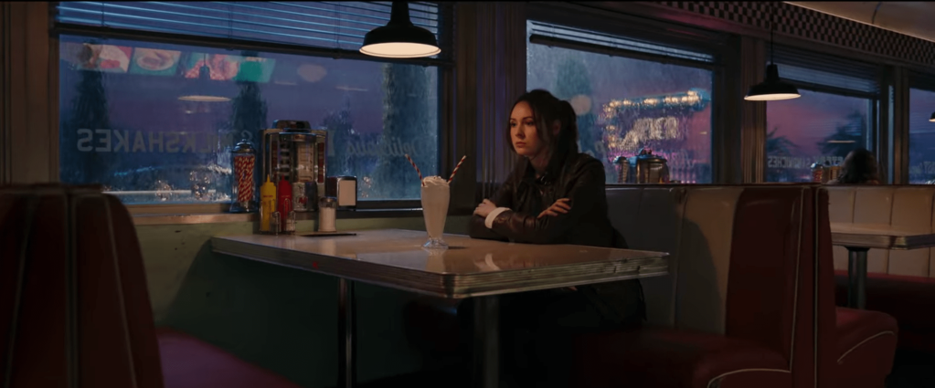 Sam sitting alone in the diner booth with a milkshake in front of her.