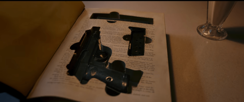 A handgun that has been taken apart and then fit into spaces that have been cut out of a book.