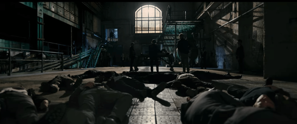 A large empty warehouse room with a single large window at the far end to light it. On the floor on the near ground are the bodies of several dead men. Farther away stand other men who are surveying the damage.