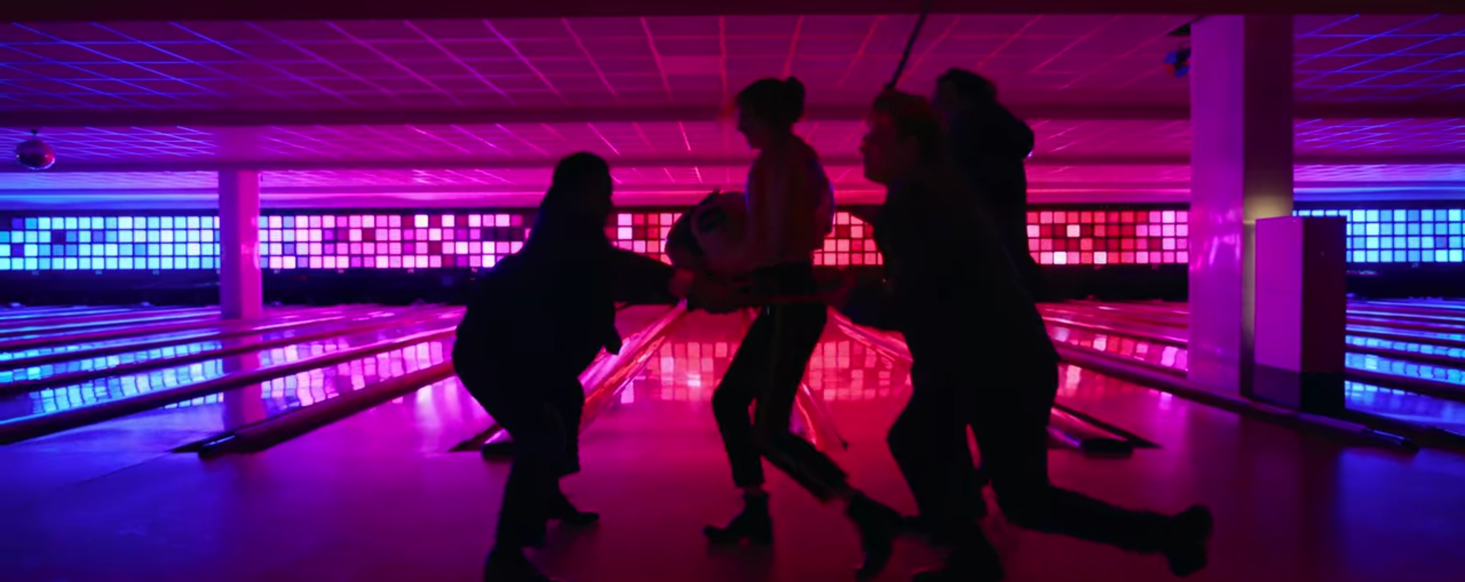 Sam in a bowling alley lit up by pink and blue squares at the end of the lanes. She is fighting off three men armed only with a child's suitcase shaped like a panda.