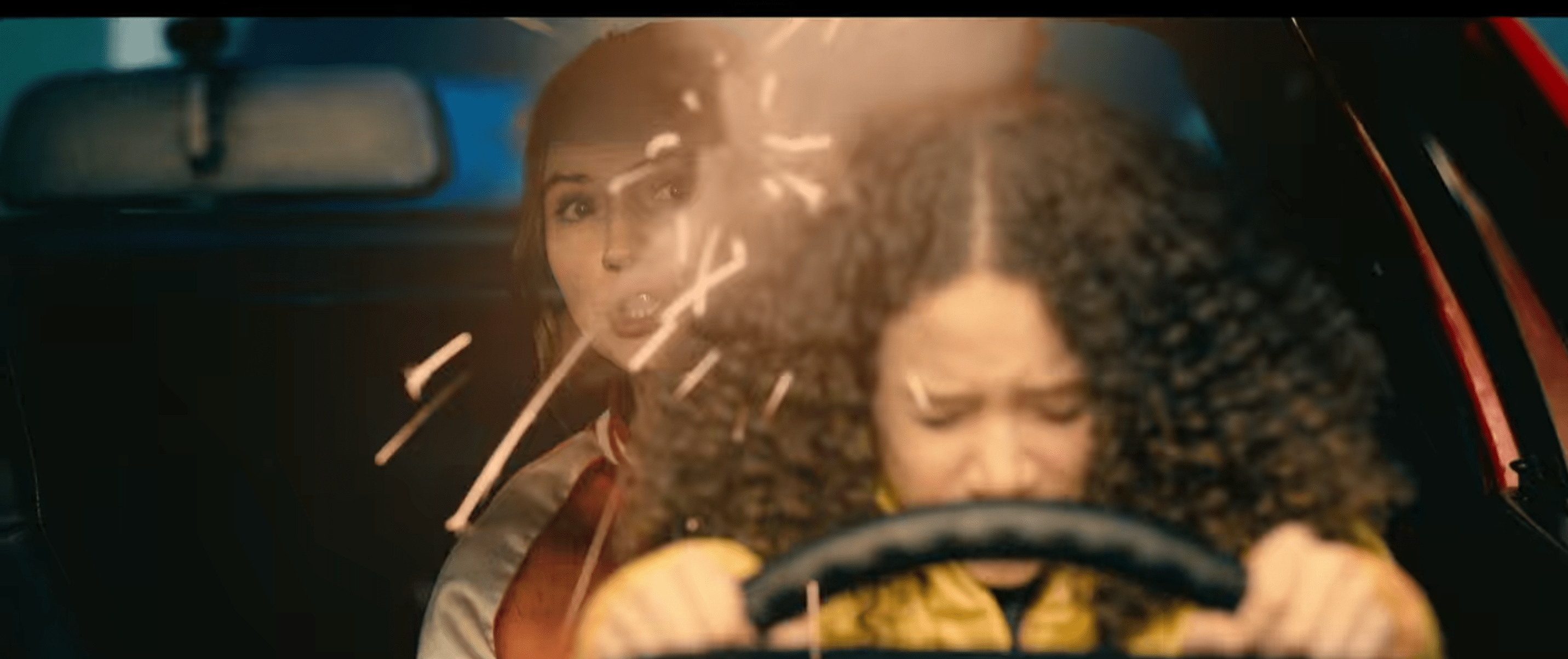 Emily holding the steering wheel while closing her eyes and tilting her head down. She is seated on Sam's lap who leans around her to see. Sam is mid-speech. The reflection of sparks is visible on their windshield.