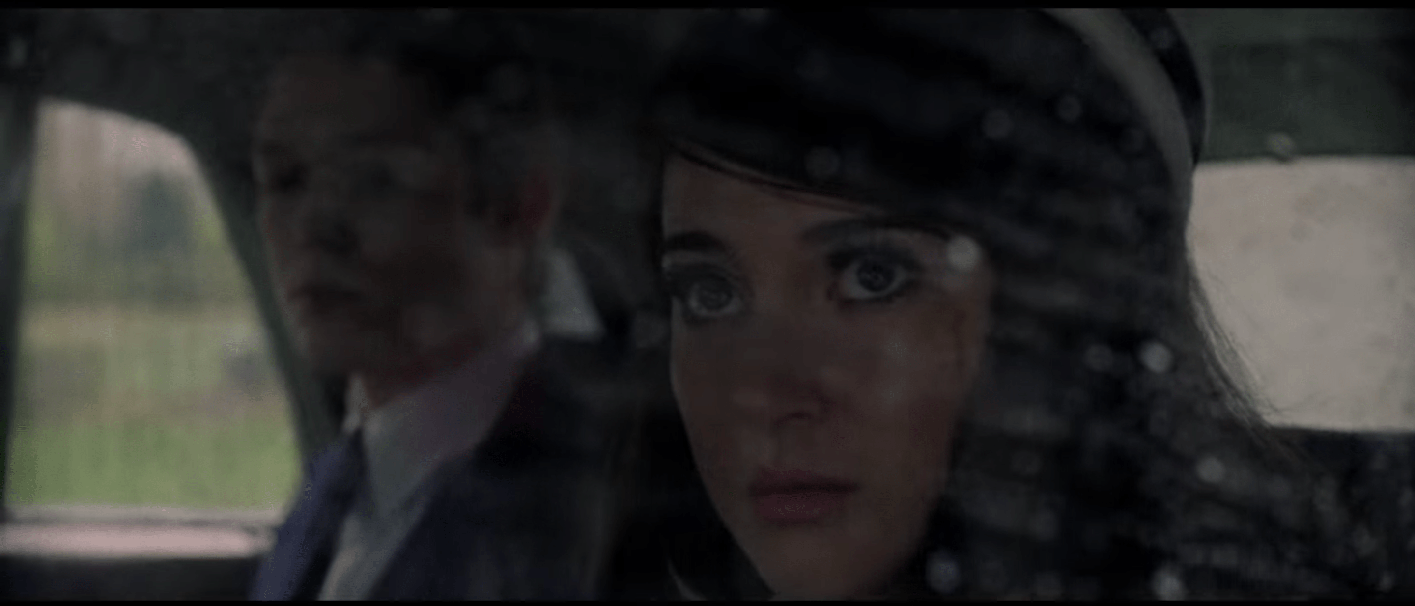 Jennifer, a scar visible below her eye, looking out and up through a rain-spotted car window. Lawrence, wearing a suit and tie