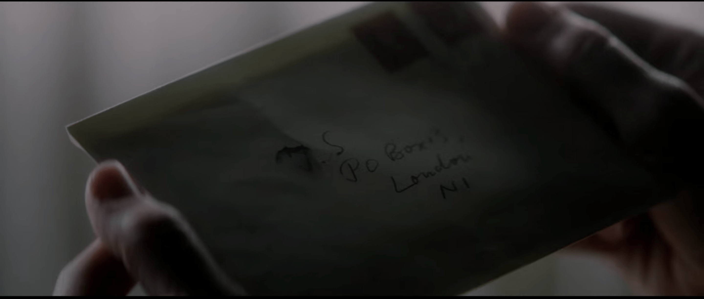 Lawrence's hands holding a letter addressed to J.S. at a P.O. Box address in London. the J is very smeared.