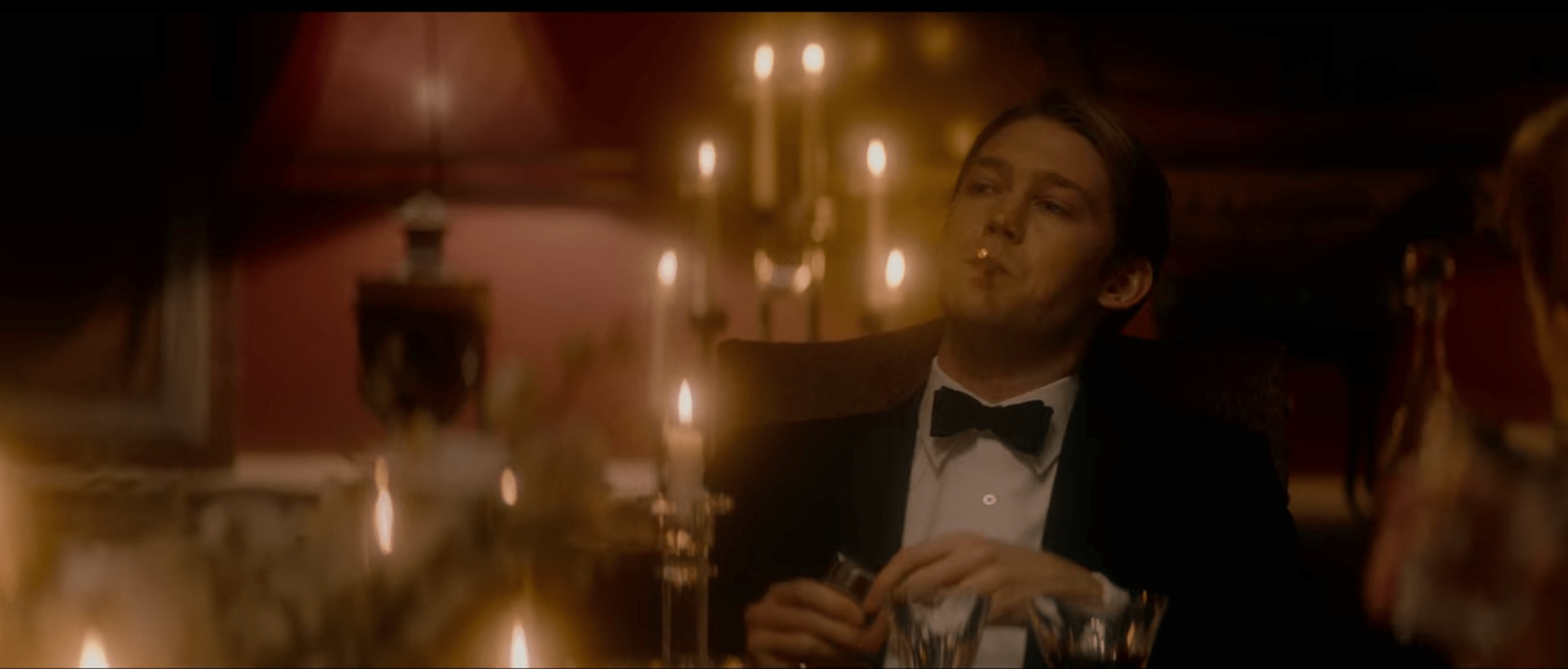 Lawrence in formal dinner attire with a cigarette in his mouth. There are lit candles glowing behind him and in front of him. His facial expression is smug.