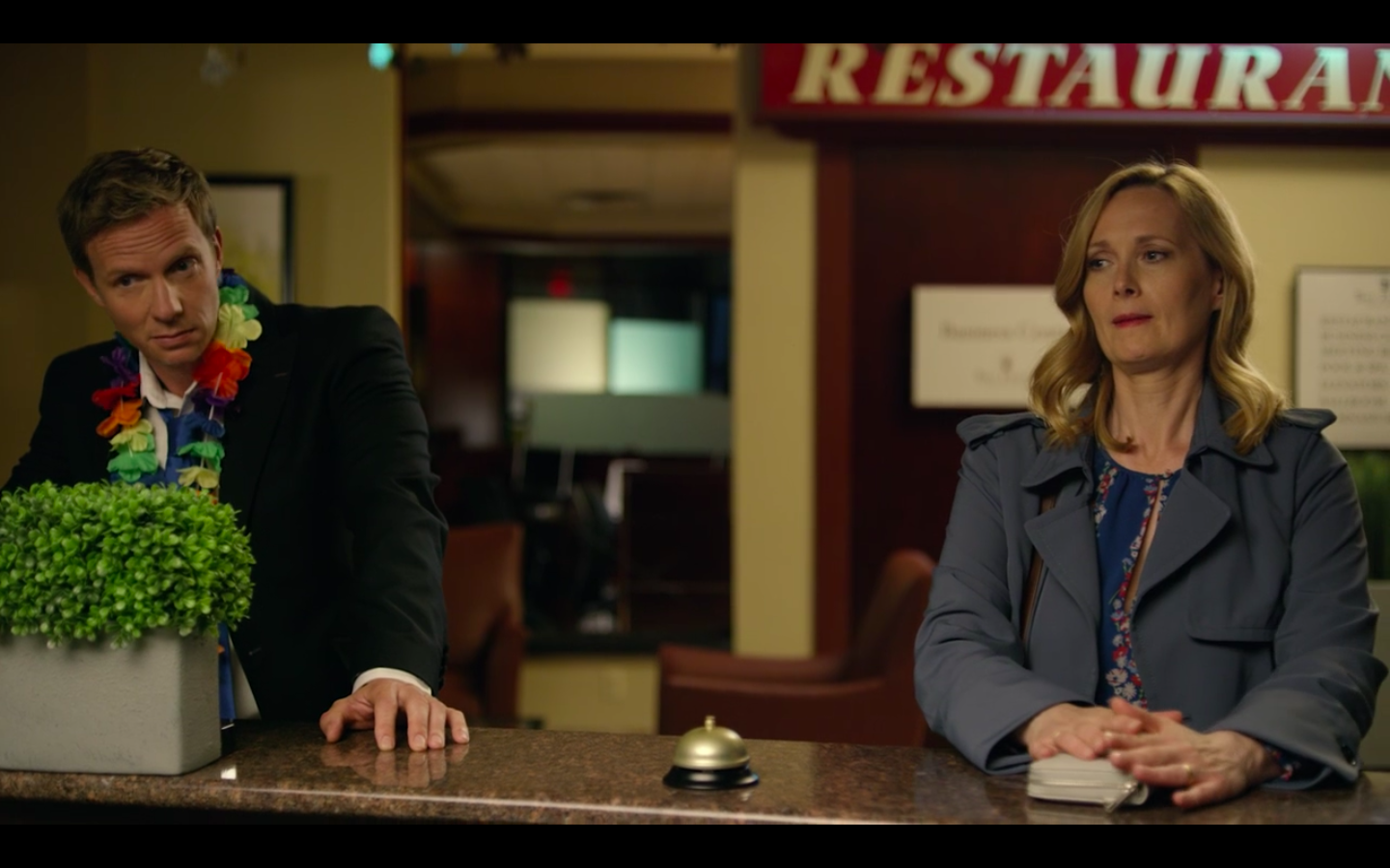 Luke, a tall blonde man wearing a suit and a plastic lei, stands next to Abby, a tall blond woman wearing a blue trench coat, they both have their hands on the hotel reception desk. A bell is between them and both are staring forward with amused, but awkward expressions on their faces.