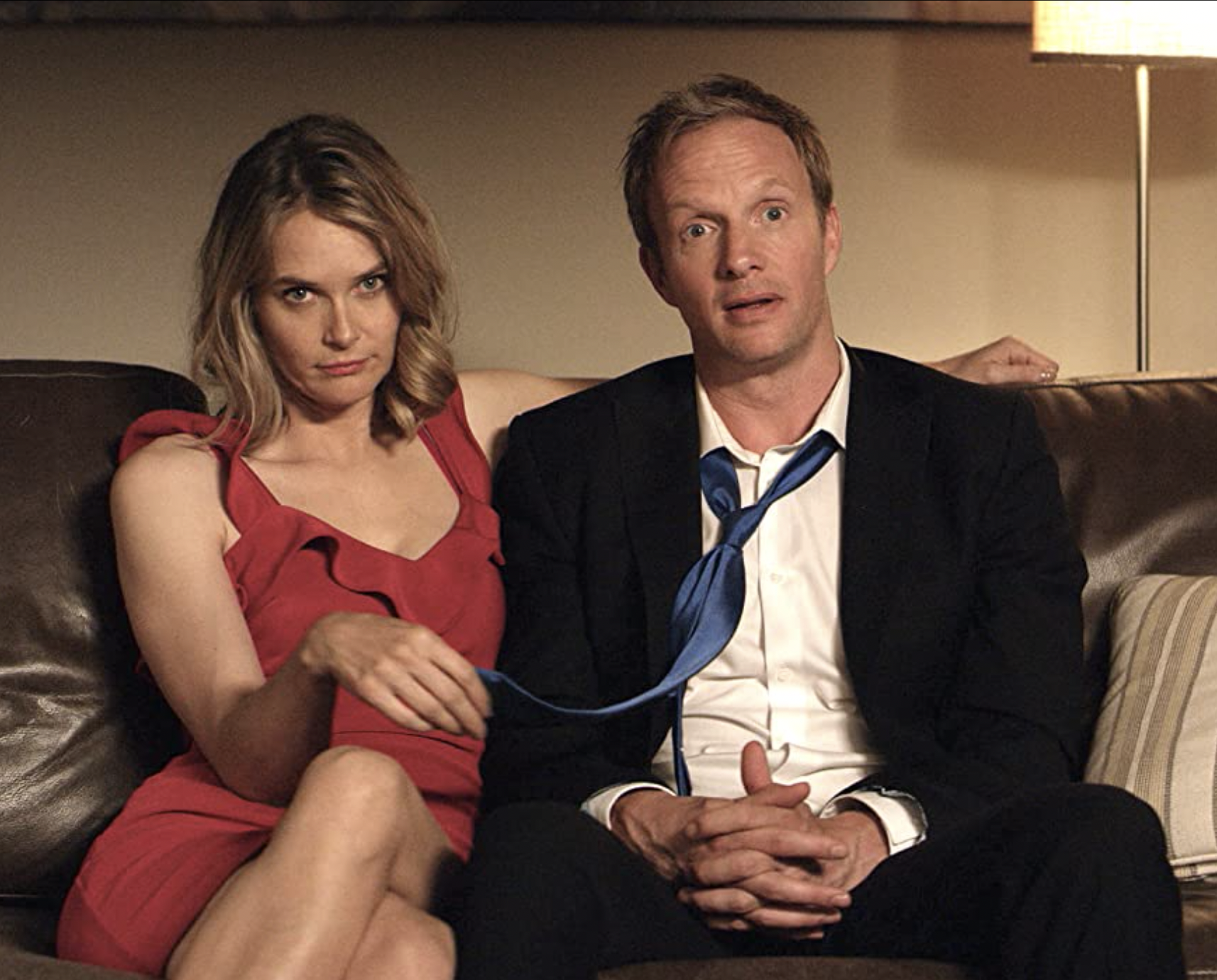 Kayla, a blonde woman in a red dress, sits very close to Luke on a brown leather couch. One of her arms is across the back of the couch while her other had plays idly with the end of his tie. He looks somewhat terrified. She looks like she is stalking something.