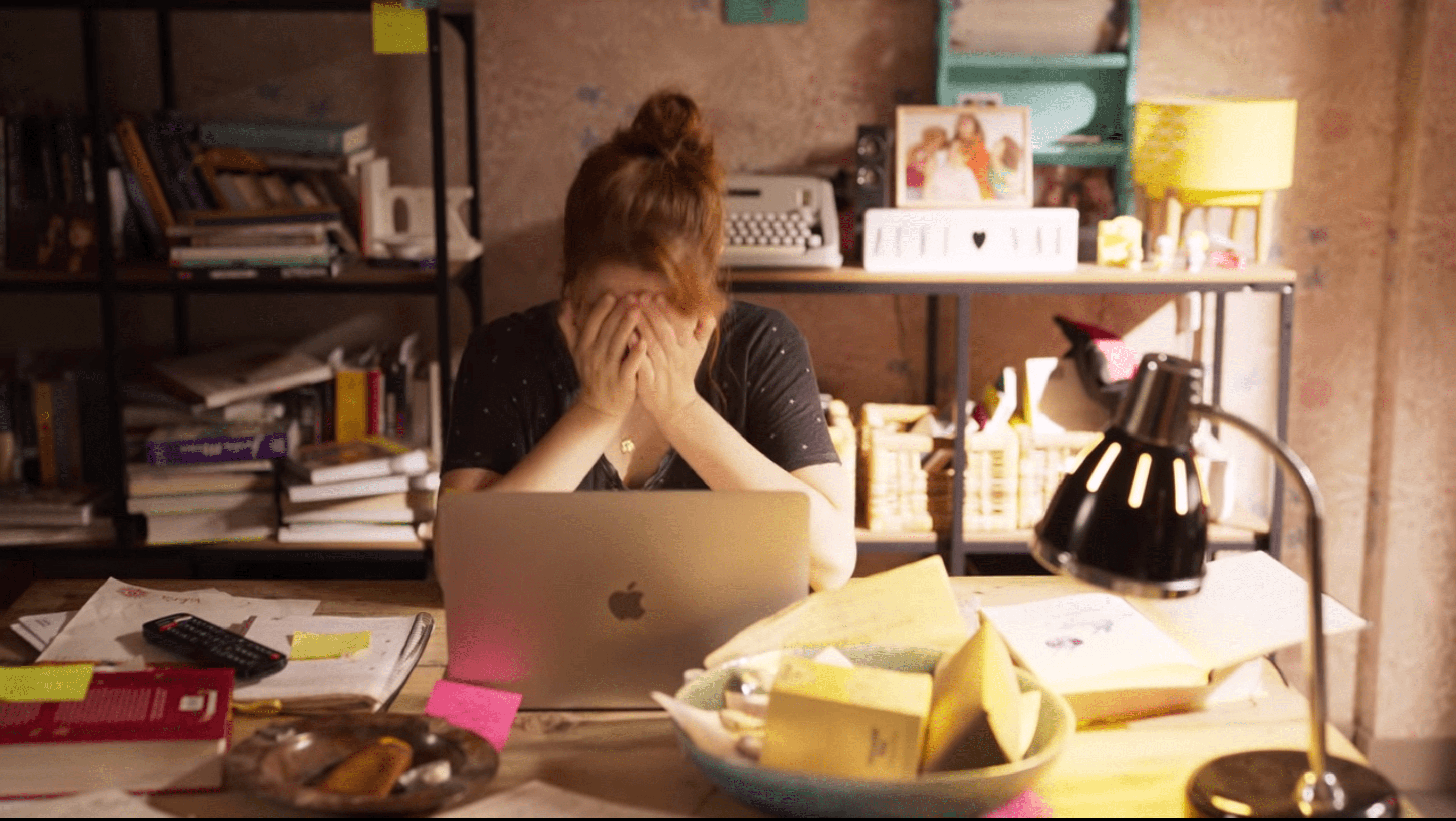 Valeria, a white woman with medium length red hair, sits in front of a lap top with her face in her hands. the desk around her is messy and so are all the book shelves behind her.
