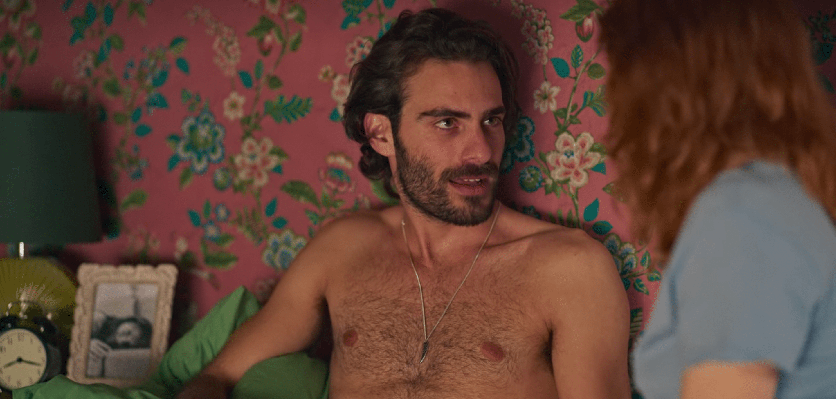 Adrian, a white man with dark brown hair and a scruffy beard, sitting shirtless against pink floral wallpaper in a bedroom. Under his arm is a green pillow and next to him is a nightstand with a black and white photo of Valeria, an old alarm clock, and a green lamp.