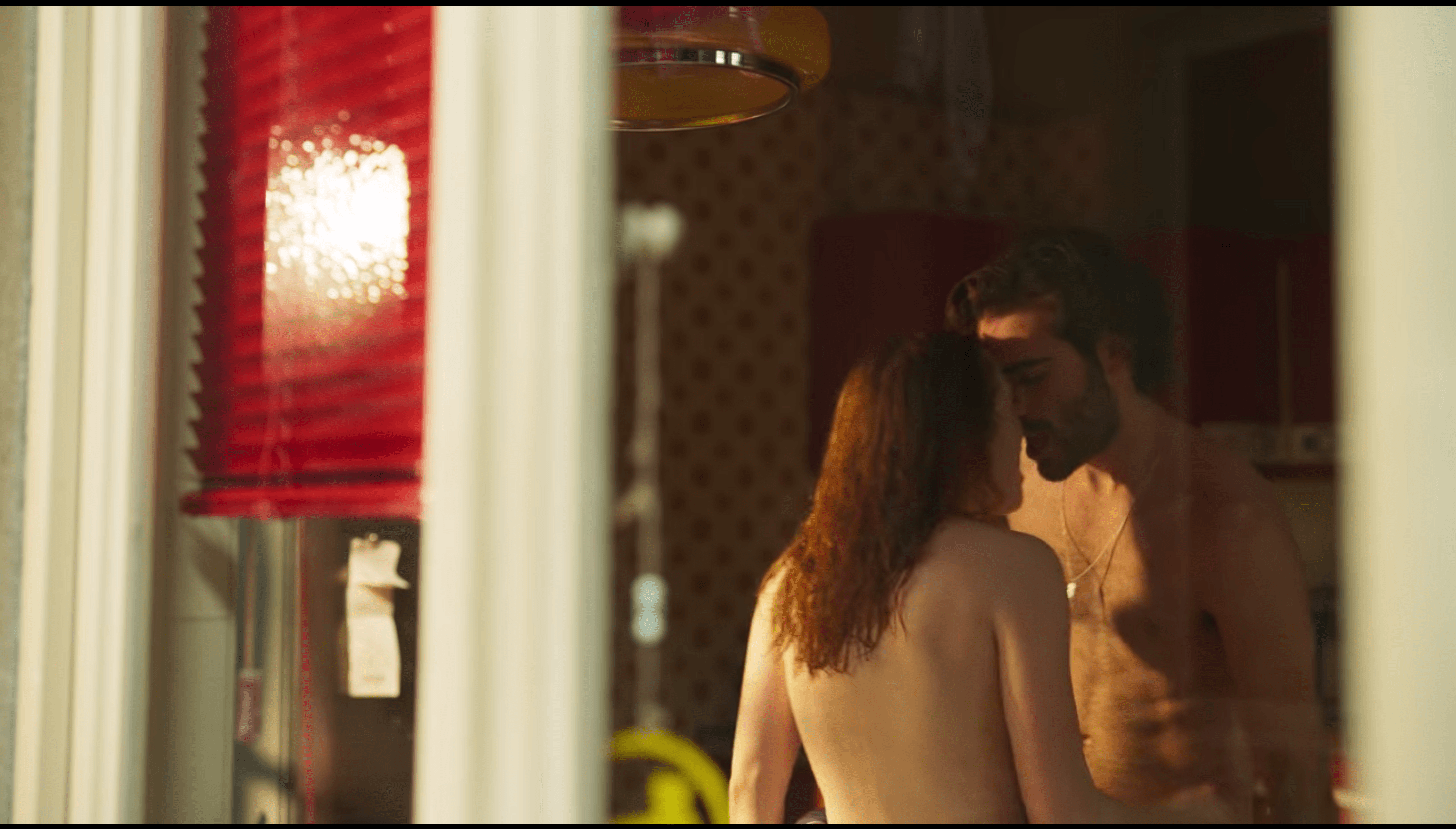 Valeria and Adrián, both topless, getting it on in their kitchen. Above them is a yellow light fixture. Behind them is a bright red slatted blind.
