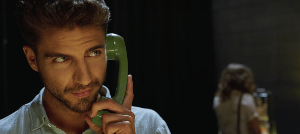 Victor holding a green landline receiver while looking to his left.