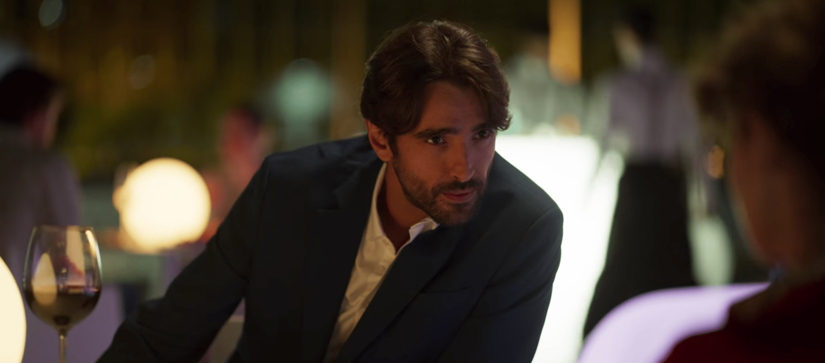 Sergio, a white man with dark hair and a scruffy beard, wearing dark blue suit jacket over a white button down leaning toward Lola over an outside table.