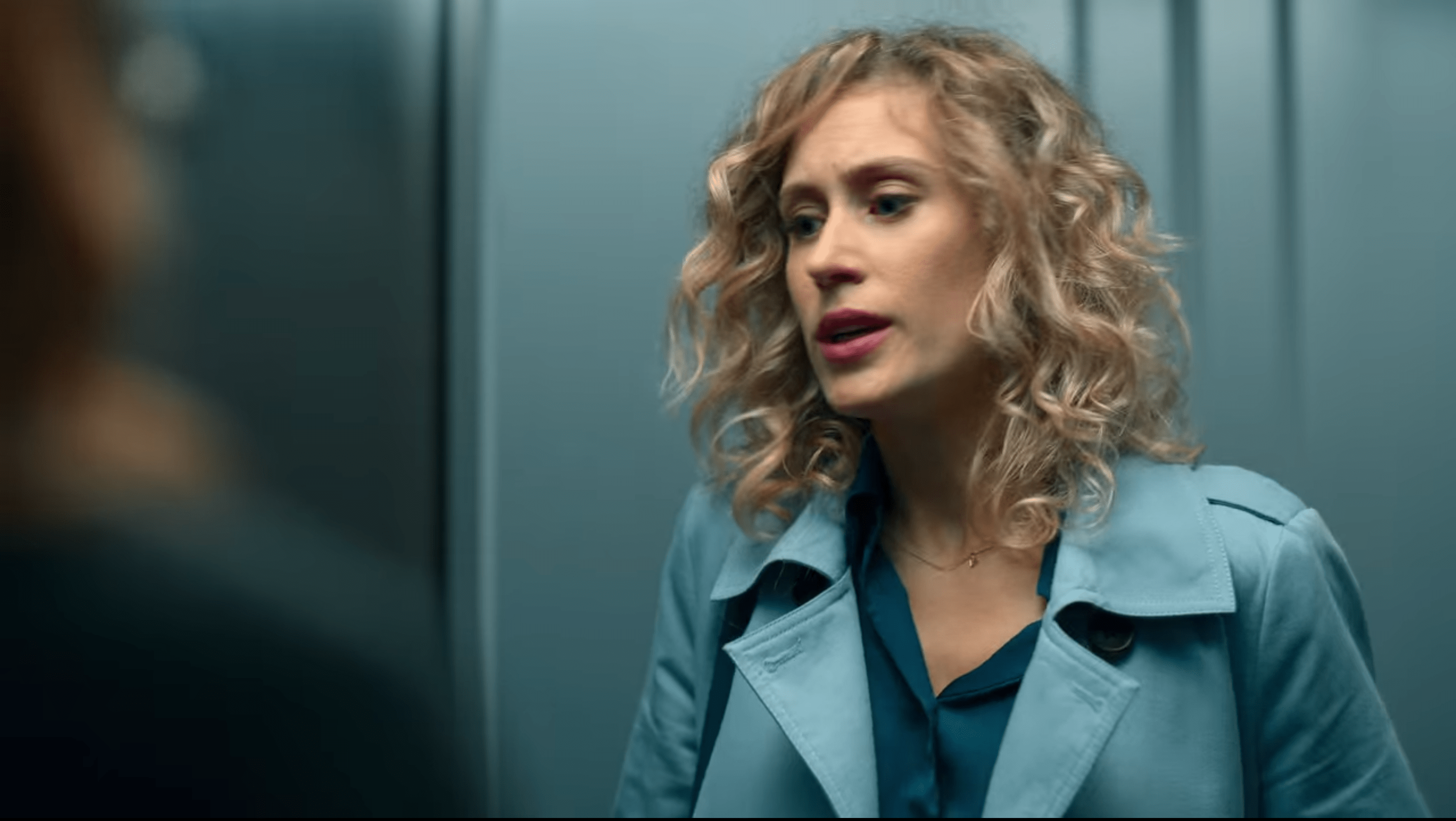 Nerea in a blue trench coat, her hair in long loose curls.
