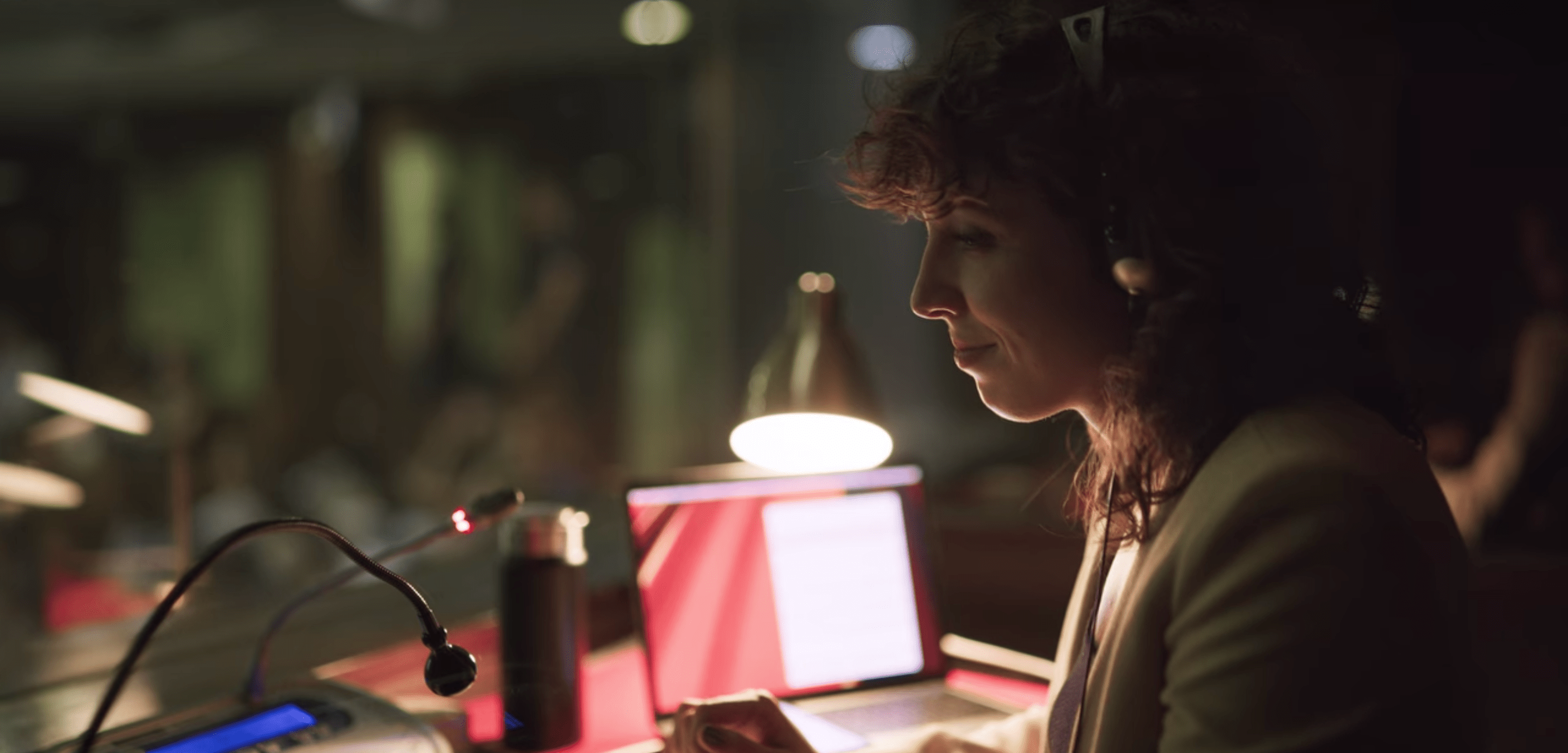 Lola, a white woman with dark, loosely curly hair, sits in an interpreter's booth wearing headphones.